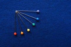 蓝色布料背景织品和针彩虹 免版税库存图片
