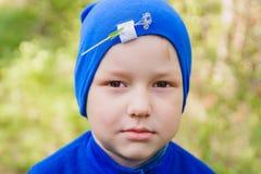 蓝色帽子的一个男孩有在他的头的一朵花的在森林 库存图片