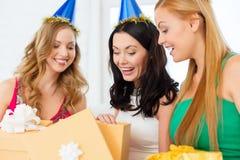 蓝色帽子的三名微笑的妇女有礼物盒的 库存图片