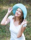 蓝色帽子的可爱的女孩在深绿色背景  图库摄影