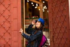 蓝色帽子的微笑的俏丽的女孩在与古色古香的红色门的老大厦附近 女性式样摆在 免版税库存照片