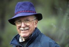 蓝色帽子的精致的老人 免版税库存照片