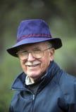 蓝色帽子的精致的老人 免版税库存图片