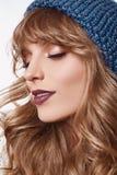 蓝色帽子的肉欲的白肤金发的妇女在白色背景 免版税库存照片
