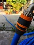 蓝色庭院水水管喷管和橙色连接器 库存照片