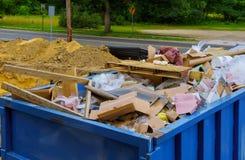 蓝色建筑废料容器用岩石和具体瓦砾填装了 工业垃圾桶 免版税库存图片