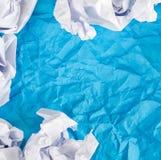 蓝色弄皱了与被弄皱的纸球的纸背景 库存图片