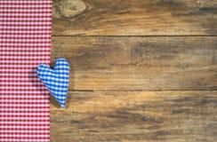蓝色心脏和红色方格的织品在土气木板 库存图片