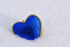 蓝色心脏的形状在雪的在冬天, 2月14日是 免版税库存照片