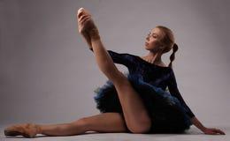 蓝色成套装备的美丽的芭蕾舞女演员在演播室坐地板并且握她的腿 免版税图库摄影