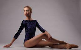 蓝色成套装备的美丽的芭蕾舞女演员在演播室,灰色背景 图库摄影