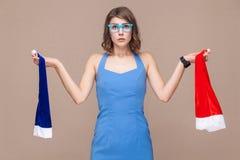 蓝色或rad盖帽?看照相机的迷茫的妇女 库存图片