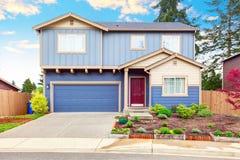 蓝色房子的好的遏制呼吁有前面庭院和车库的 库存图片