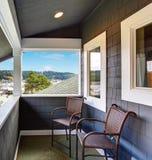 蓝色房屋板壁家的被盖的门廊有两把椅子的 库存图片