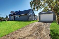 蓝色房屋板壁房子后院视图有独立式车库的 库存照片