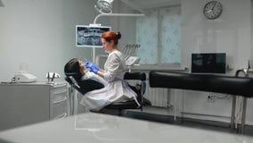 蓝色手套和一件白色外套的女性医生接近对患者的椅子和使用的X-射线和的仪器 影视素材