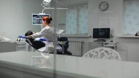 蓝色手套和一件白色外套的女性医生接近对患者的椅子和使用的X-射线和的仪器 股票录像