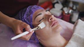 蓝色手套的一名美容师在年轻女人上的面孔把与一把白色刷子的一个透明胶凝体放 ??  股票视频
