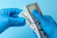 蓝色手套的医生拿着金钱在蓝色背景的现金美元 贿款、腐败或者薪金的概念 免版税库存照片