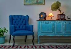 蓝色扶手椅子,葡萄酒木浅兰的餐具柜,点燃了古色古香的台灯、老留声机留声机和唱片 免版税库存照片