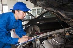 去蓝色技术员的制服的人为maintenan的汽车修理 免版税库存照片