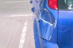 蓝色抓了有损坏的油漆的汽车在崩溃事故或停车场并且消弱了金属身体损伤从碰撞的 库存图片
