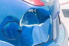 蓝色抓了有损坏的油漆的汽车在崩溃事故或停车场并且消弱了金属身体损伤从碰撞的 免版税图库摄影