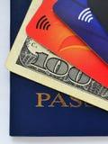 蓝色护照、一百元钞票和三张不同信用卡 免版税图库摄影