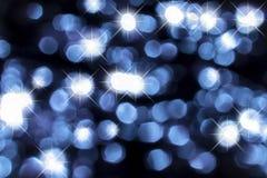 蓝色抽象背景的光Bokeh和闪闪发光 免版税图库摄影