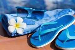 蓝色拖鞋、太阳镜和毛巾在游泳池的边界 免版税库存图片