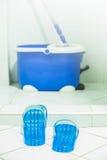 蓝色拖鞋、拖把和桶 免版税库存图片