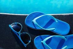 蓝色拖鞋和太阳镜临近游泳池假日概念 库存图片