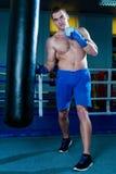 蓝色拳击手套的英俊的人训练在健身房的一个沙袋的 做锻炼的男性拳击手 免版税库存照片