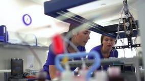 蓝色控制药物制造业的制服和橡胶手套的画象两年轻女人在实验室里 ?? 股票视频
