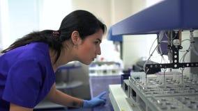 蓝色控制药物制造业的制服和橡胶手套的画象年轻女人在实验室里 ?? 影视素材