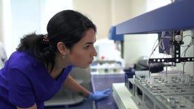 蓝色控制药物制造业的制服和橡胶手套的画象年轻实验室妇女在实验室里 ?? 股票录像
