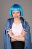 蓝色摆在与横渡的胳膊的假发和外套的微笑的夫人 关闭 灰色背景 库存照片