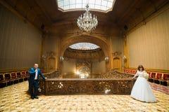 蓝色摆在老冰屑玻璃天花板前面的葡萄酒房子的衣服和俏丽的新娘佩带的白色礼服的典雅的新郎  图库摄影