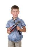 蓝色方格的衬衣的逗人喜爱的小男孩,拿着大厦仪器,隔绝在白色背景 免版税库存图片