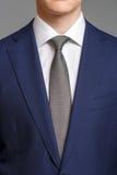 蓝色无尾礼服的人有灰色领带的 免版税库存照片