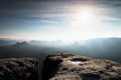 蓝色春天破晓 在深有薄雾的谷上的砂岩峭壁在萨克森瑞士 多小山峰顶 图库摄影