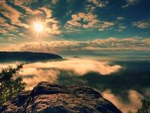 蓝色有薄雾的破晓 在深有雾的谷上的砂岩峭壁在山 库存图片