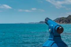 蓝色望远镜-游人的全景双筒望远镜有海视图 免版税库存图片