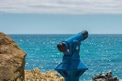 蓝色望远镜-游人的全景双筒望远镜有海视图 免版税图库摄影