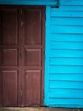 蓝色木墙壁和绯红色木门 免版税库存照片