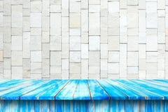 蓝色木桌被堆积的石墙 免版税图库摄影