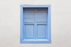 蓝色木窗口是在白水泥墙壁上的经典葡萄酒样式 库存照片