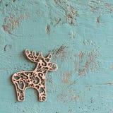 蓝色木表面和木圣诞节鹿 免版税库存照片