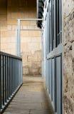 蓝色木门构筑的狭窄的导致石墙的段落和楼梯栏杆 库存图片