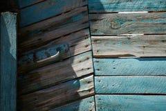 蓝色木门由有金属把柄的委员会做成 免版税图库摄影